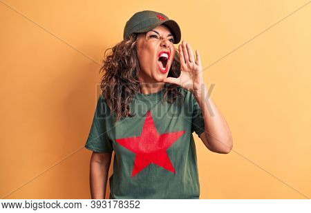 Middle age brunette woman wearing t-shirt and cap with red star symbol of communism shouting and screaming loud to side with hand on mouth. Communication concept.