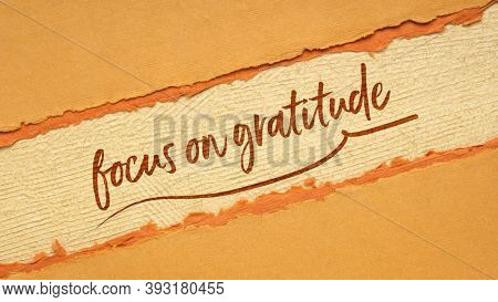 focus on gratitude - inspirational handwriting on a handmade paper in orange and brown tones, web banner, Thanksgiving theme