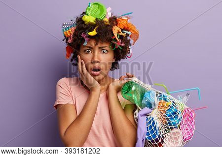 Puzzled Stupefied Dark Skinned Woman Holds Bag Filled With Plastic Wastes, Shocked With Problem Of E