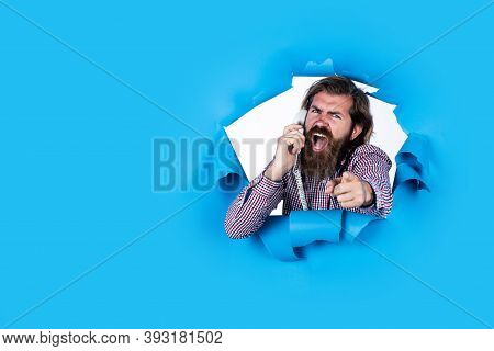 Unpleasant Phone Call. Brutal Bearded Man Shouting Into Telephone Receiver. Angry Man Torn Blue Back