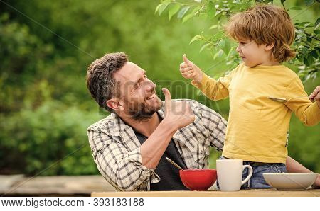 Menu For Children. Homemade Meal. Food Habits. Little Boy With Dad Eating Food Picnic Yard Nature Ba