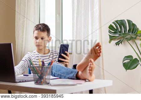 Kid Distracting From Online Lesson Or Homework And Playing Video Games, Scrolling Phone, Texting On