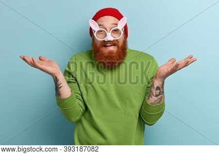 Funny Cheerful Bearded Man Wears Round Rabbit Glasses With Ears, Has Tattoos, Spreads Palms, Doesnt
