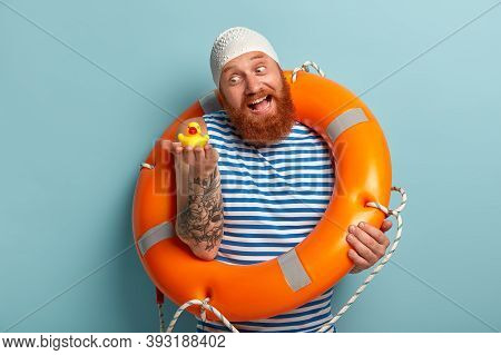 Playful Joyous Man With Red Thick Beard, Holds Small Toy Duckling, Has Fun On Shore, Enjoys Safe Swi
