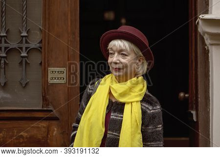 An Elderly Woman 60-65 Years Old In A Hat Comes Out Of The Entrance Of An Old House. Concept, Retire
