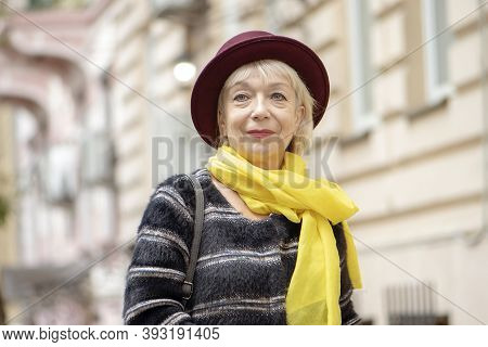 An Elderly Woman 60-65 Years Old Adjusts A Fashionable Hat On The Background Of The City Landscape.