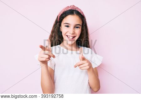 Cute hispanic child girl wearing casual clothes and diadem pointing fingers to camera with happy and funny face. good energy and vibes.