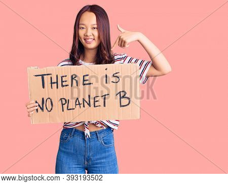 Young beautiful chinese girl holding there is no planet b banner pointing finger to one self smiling happy and proud