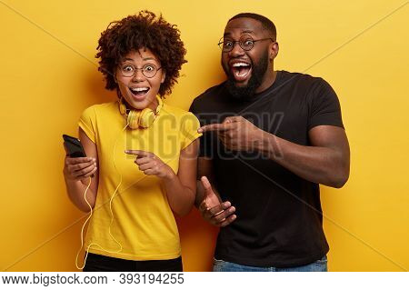 Hey, Have Look At Screen Of Cellular. Horizontal Shot Of Overjoyed African American Woman Has Headph