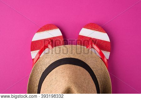 Top Above Overhead View Photo Of A Pair Of Flipflops And A Hat Isolated On Pink Background