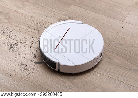 A White Robot Vacuum Cleaner Removes Debris On The Floor Of The Laminate. High Quality Photo