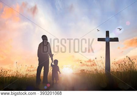 Family Worship And Holy Bible Story Concept: Silhouette Father And Son Looking For The Cross On Mead