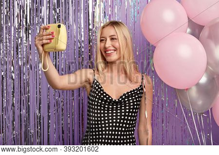 Attractive Blonde European Woman With Shining Smile, Wears Polka Dot Dress, Makes Selfie With Small
