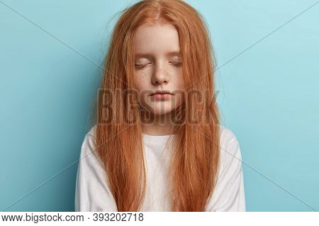 Close Up Shot Of Attractive Redhead Little Girl Keeps Eyes Shut, Feels Sleepy Late In Evening, Waits