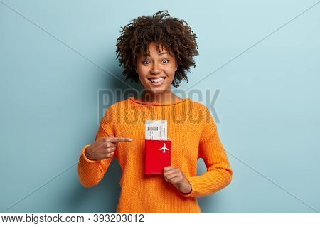 Photo Of Glad Dark Skinned Curly Female Traveller Points At Tickets And Passport, Rejoices Having Tr
