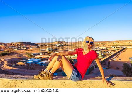 Tourist Woman Sitting By Panoramic View Of Coober Pedy Underground Town At Sunset And Surrounding De