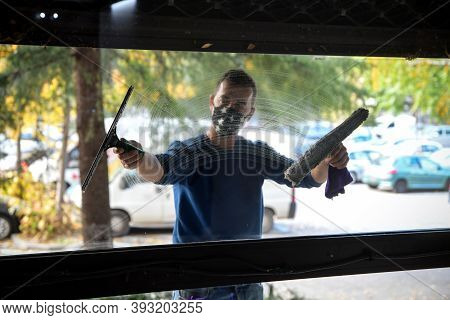 Cleaning The Window. A Young Man With Mask On The Face Cleans And Polishes Windows With A Sponge