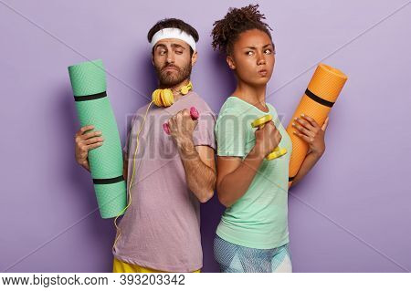 Diverse Sporty Couple Stand Backs, Hold Dumbbells, Fitness Mats, Has Confident Determined Facial Exp
