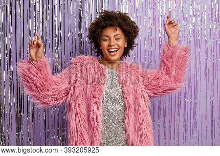 Beautiful Carefree Excited Woman With Makeup, Wears Shiny Dress And Pink Fur Coat, Raises Hands As D