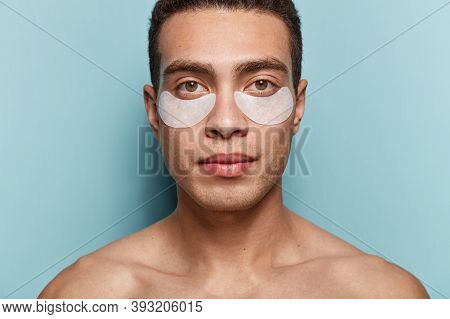 Cosmetology For Men. Serious Handsome European Male Youngster With Patches Under Eyes, Has Muscular