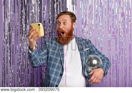 Photo Of Stupefied Caucasian Man With Red Hair And Beard, Holds Disco Ball Under Arm, Looks Surprisi