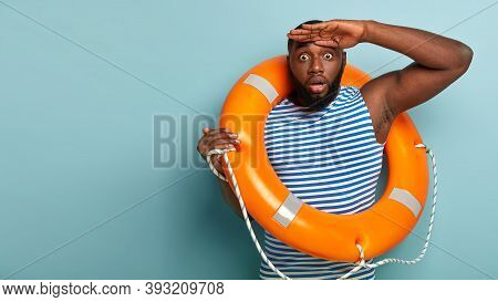 Horrified Black Male Rescuer Holds Palm Near Forehead, Focused Into Distance, Shocked By Hazard Situ
