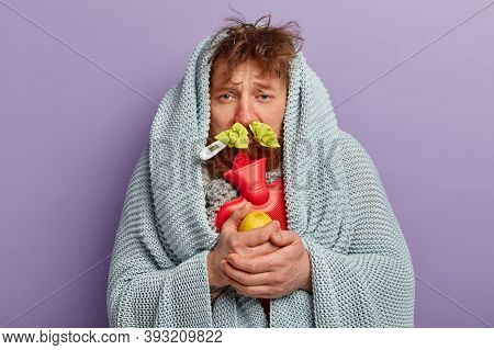 Medical Treatment Concept. Bearded Ill Foxy Man Wrapped In Coverlet, Holds Hot Water Bottle, Carries