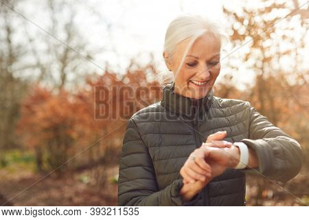 Senior Woman Running In Autumn Countryside Exercising Checking Smart Watch Fitness Activity App