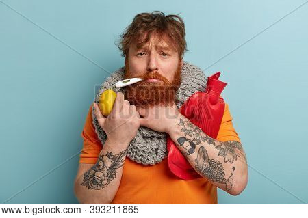 Redhead Upset Man Keeps Thermometer In Mouth, Suffers From Fever, Holds Lemon, Hot Water Bottle, Wea