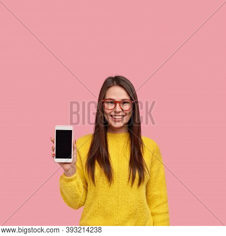 Vertical Shot Of Happy Female Shop Assistant Advertises New Device, Holds Smart Phone With Empty Scr