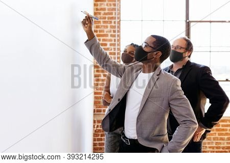 Business people wearing masks brainstorming on a whiteboard, the new normal