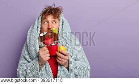 Traditional Treatment Concept. Stunned Ill Man Drinks Hot Milk With Honey, Eats Lemon, Cures Cold, H