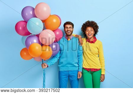 Young Couple Come On Party, Man Holds Bunch Of Many Colorful Balloons, His Girlfriend Stands Near, W