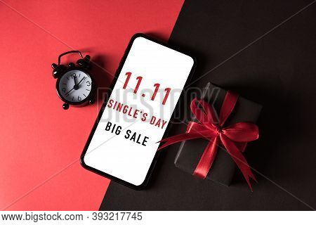 11:11 Sale Shopping Concept, Top View Of Gift Box Wrapped In Black Paper And Bow Ribbon And Mobile S