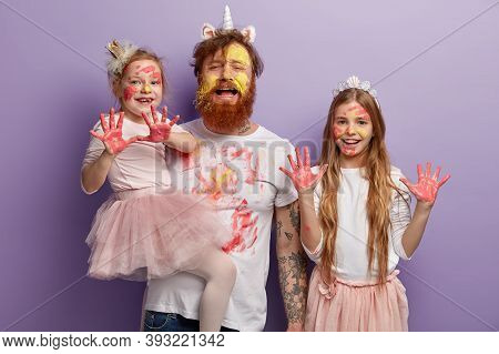 Fatigue Redhead Bearded Dad Smeared With Yellow And Red Watercolors, Spends Free Time With Two Naugh