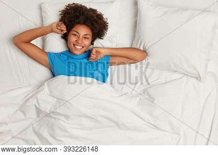 Smiling Lovely Woman With Afro Haircut Stretches In Bed After Awakening, Dressed In Pyjamas Wakes Up