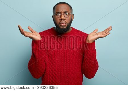 Angry Disappointed Black Man Spreads Hands With Indignation, Looks With Uncertainty, Has Dark Stubbl