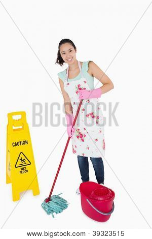 Woman cleaning near a caution wet floor sign