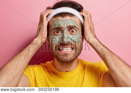 Embarrassed Handsome Man Has Clay Mask On Face For Cleansing Skin, Keeps Both Hands On Head, Wears W