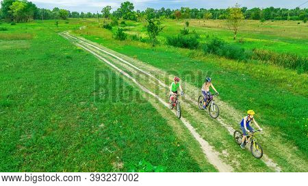 Family Cycling On Bikes Outdoors Aerial View From Above, Happy Active Mother With Children Have Fun,