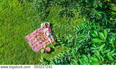 Beautiful Young Girl Relaxing On Grass, Having Summer Picnic In Park Outdoors, Aerial Drone View Fro