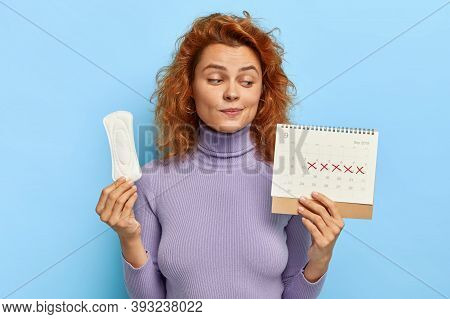 Photo Of Young Woman Looks At Period Calendar, Checks Menstruation Days, Holds Soft Sanitary Pad, Pu