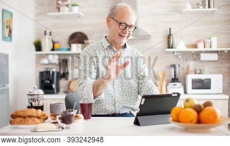 Authentic Senior Man On Online Video Call In The Morning In Cozy Kitchen. Elderly Person Using Inter