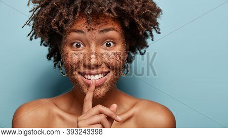 Glad Afro American Woman Smiles Broadly, Shows Hush Gesture, Looks With Secrecy And Happiness, Has C