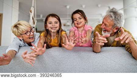 Grandchildren Having Fun, Playing With Grandparents At Home