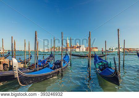 Gondolas Moored Docked On Water In Venice. Gondoliers Sailing San Marco Basin Waterway. San Giorgio