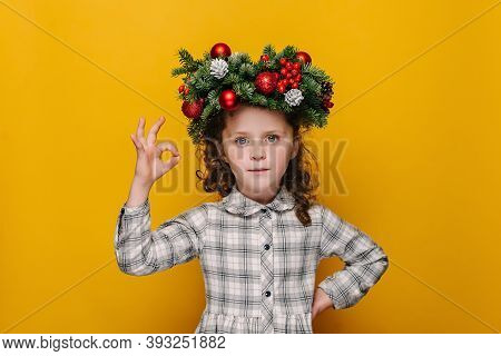 Cute Little Girl Kid In Traditional Christmas Wreath, Makes Okay Gesture, Enjoys Life, Isolated Over