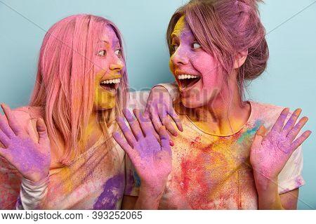 People, Joy, Celebration Concept. Portrait Of Merry Joyous Young Women Gaze At Each Other Happily, R