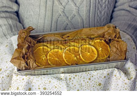 Gluten-free Homemade Orange Cake In Baking Dish With  White Napkin Held By Male Hands, Close-up.  Ho