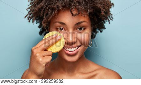 Close Up Shot Of Young Woman Cleans Face With Exfoliating Yellow Sponge, Removes Cream From Skin, St